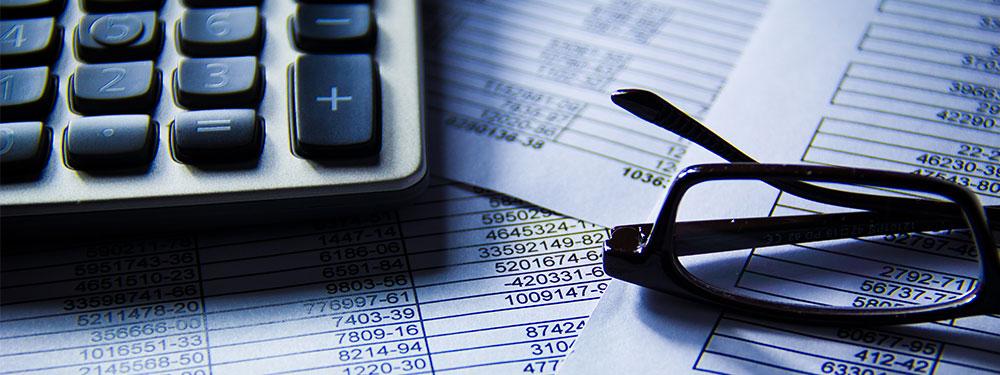 Photo d'un bureauavec une calculatrice et des feuilles de calculs