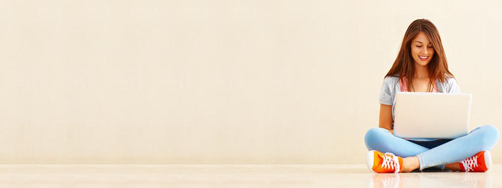 Jeune fille en tailleur consultant son ordianteur portable