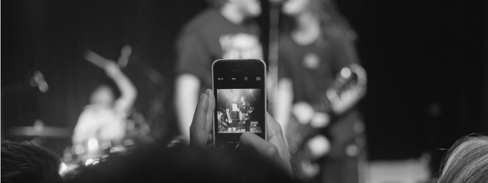 Photo d'une personne prenant la photo d'un artiste lors d'un concert