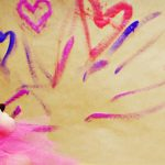 Photo d'un enfant en tutu dessinant des coeurs sur un mur