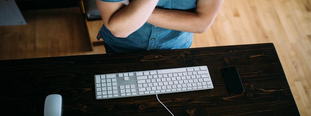 Photo d'un Jeune homme devant un clavier d'ordinateur