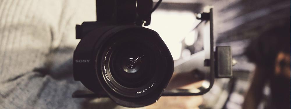 Photo d'un homme portant une caméra professionnelle à la main