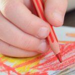 Photo d'une main d'enfant en train de dessiner