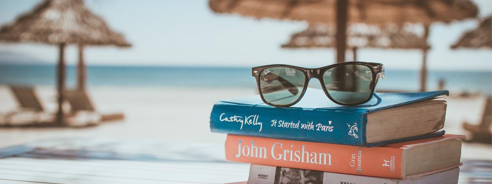 Photo de 3 livres posés sur une table sur la plage avec des lunettes de soleil posées sur le dessus