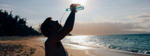 Photo d'un homme en train de boire de l'eau sur une plage