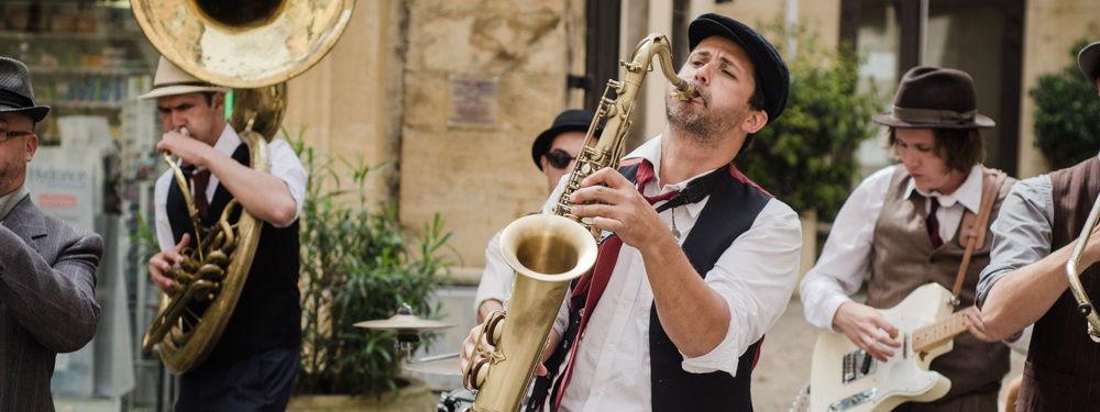Photo d'une fanfare de rue avec un saxophoniste, un trombone et une guitare electrique