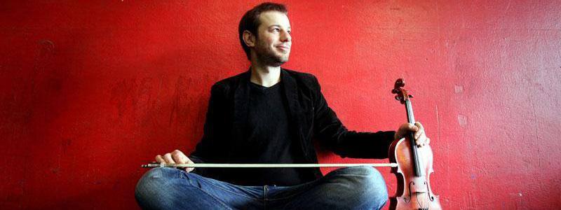 Photo de Tony assis contre un mur rouge tenant à la main son violon