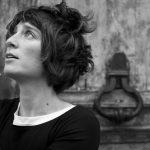 Photo NB d'une artiste en train de contempler le ciel les 2 mains ouvertes devant une lourde porte en bois