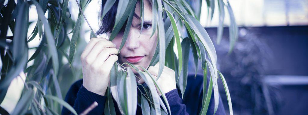 Photo de Lily Lucas semi caché derrière les feuilles d'une plante