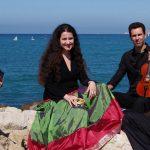 Photo de quatre musiciens qui prennent la pose devant la mer