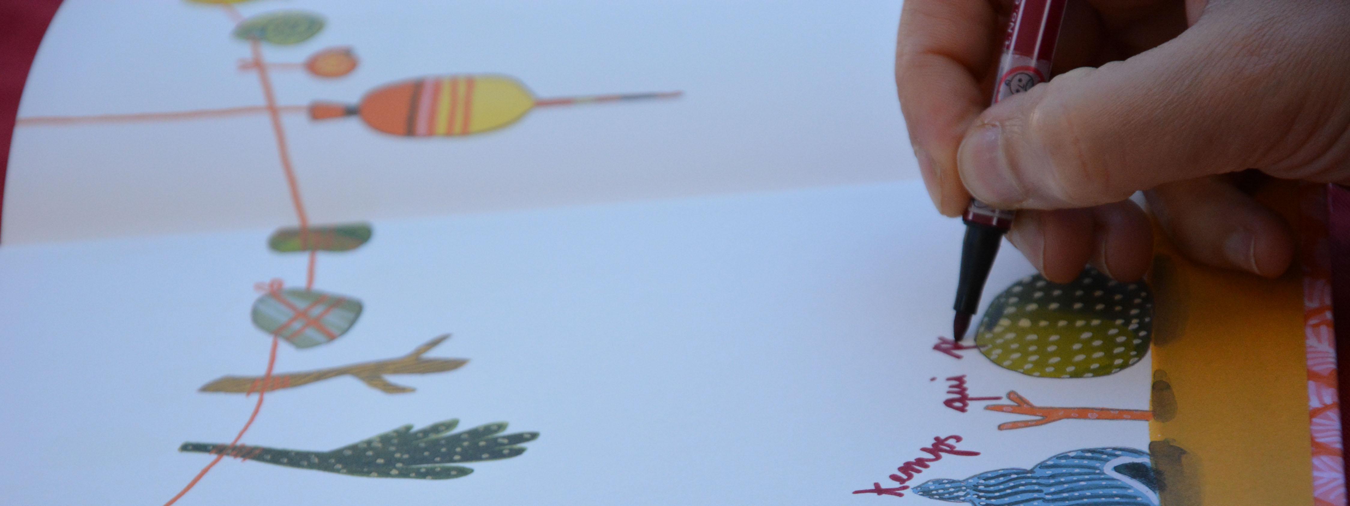 Photo d'un illustrateur en train de dédicacer un album jeunesse
