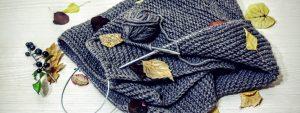 Photo d'une écharpe en laine non terminée avec des feuilles d'automne posées dessus et autour