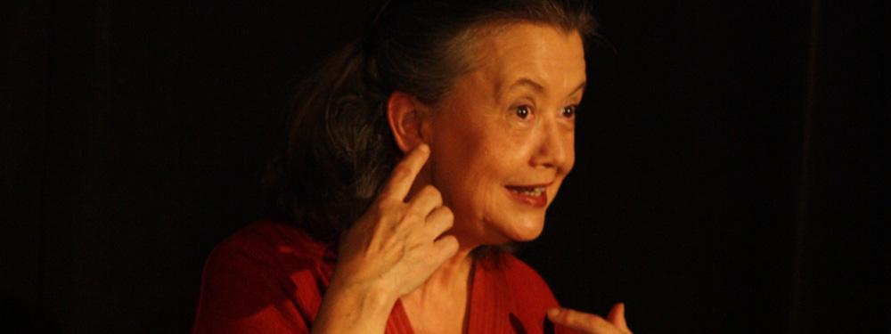 Photo de la conteuse sur scène en représentation se touchant l'oreille