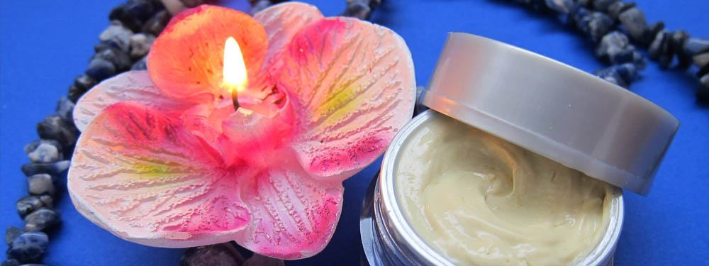 Photo d'un pot de crème à côté d'une bougie en forme de fleur
