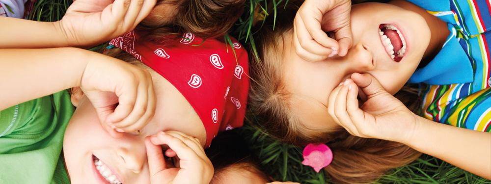 Photo d'enfants couchés dans l'herbe faisant des lunettes avec leurs mains