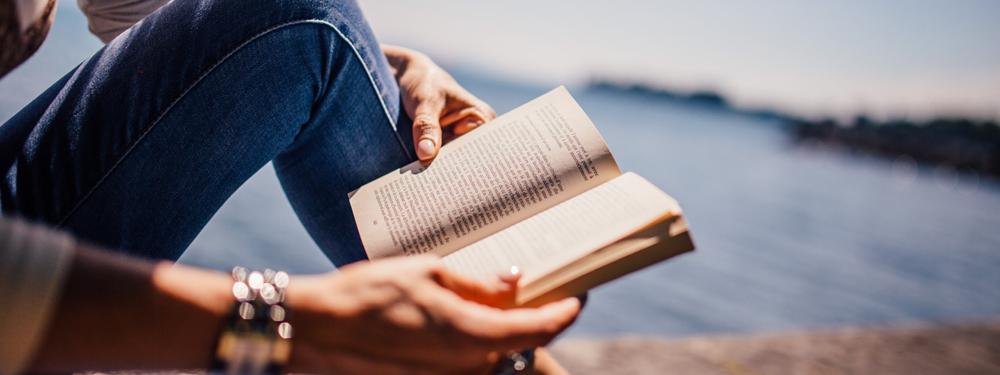 Photo d'une femme en train de lire sur un ponton