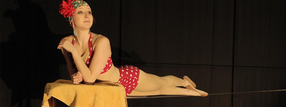 Photo d'une femme portant un maillot de bain des années 50 avec un bonnet et des ballerines de danseuse le haut du corps allongé sur une table et les jambes étendues sur un fil d'acrobate