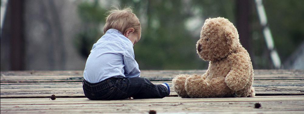 Photo d'un garçon de 1/2 ans assis par terre sur un sol en bois en face de son ours en peluche