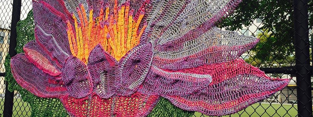 Photo d'un grillage recouvert de tricot en forme de fleurs représentant une nouvelle sorte de street art