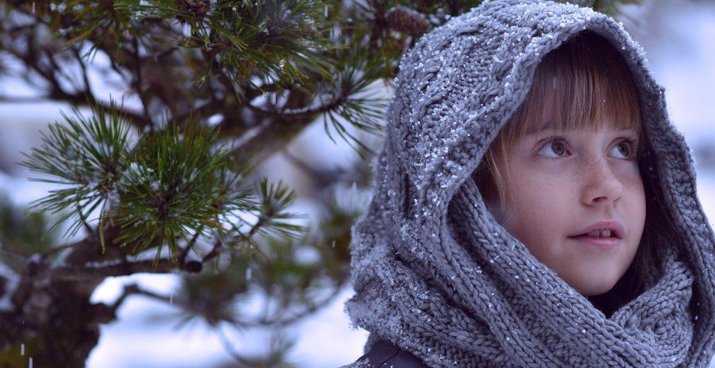 Photo d'une fillette avec une écharpe tricotée enroulée sur la têtesous la neige