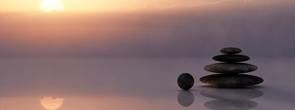Photo de paysage au couché du soleil avec des galets les uns sur les autres posés au premier plan de la photo