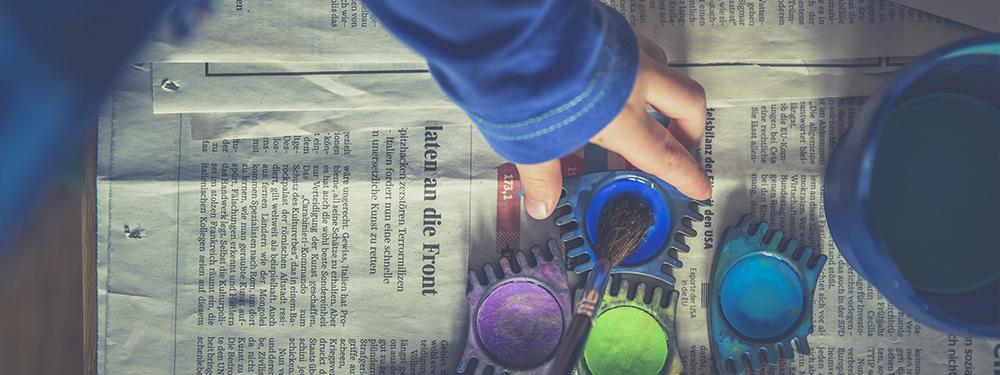 Photo representant les mains d'un enfant en train de mettre de la peinture à l'eau sur un pinceau le tout posé sur un papier journal