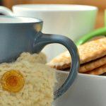 Photo d'une tasse de thé recouverte de tricot avec des petits gateaux à côté