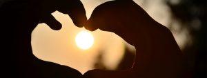 Photo de 2 mains formant un coeur au couché du soleil