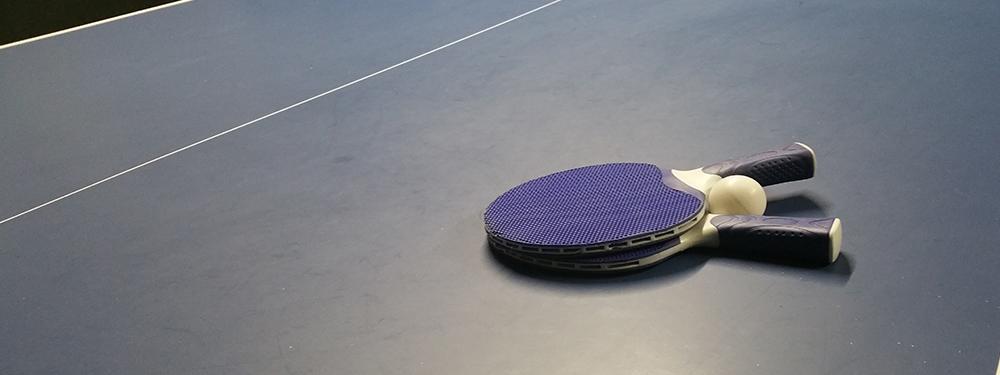 Photo de 2 raquettes de ping pong et une balle posées sur une table de ping pong