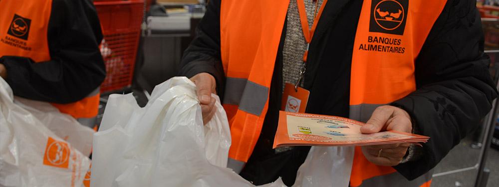Photo d'un bénévole de la banque alimentaire tenant d'une main un sac vide à distribuer et de l'autre des tracts