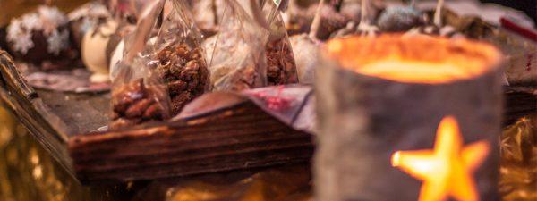 Photo de détail de mets vendus sur le marché de Noel : bougies éclairées, chocolats, pralines…