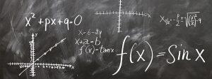 Photo d'un tableau noir avec écrit à la craie des formules mathématiques