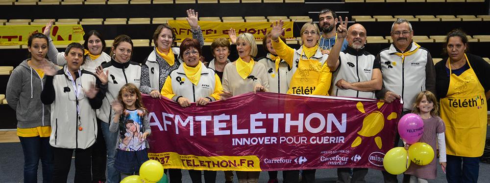 Photo de l'équipe du téléthon portant la bâche du téléthon