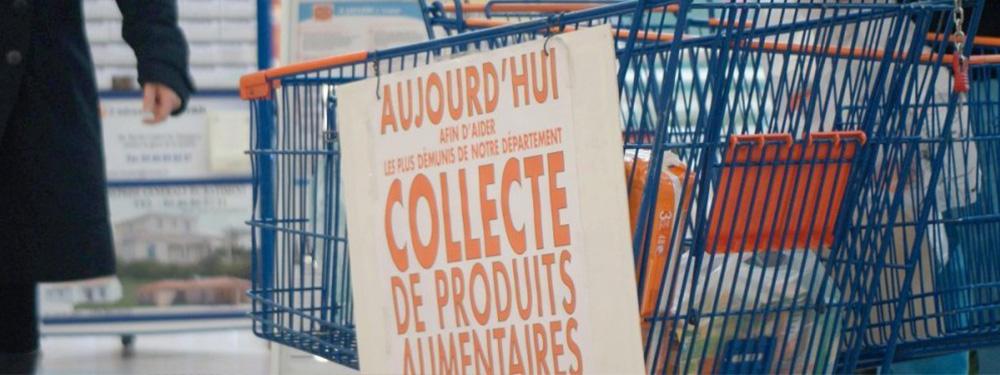"""Photo d'un caddie dans un supermarché avec une pancarte posée dessus """"Aujourd'hui afin d'aider les plus démunis du département, collecte de produits alimentaires"""