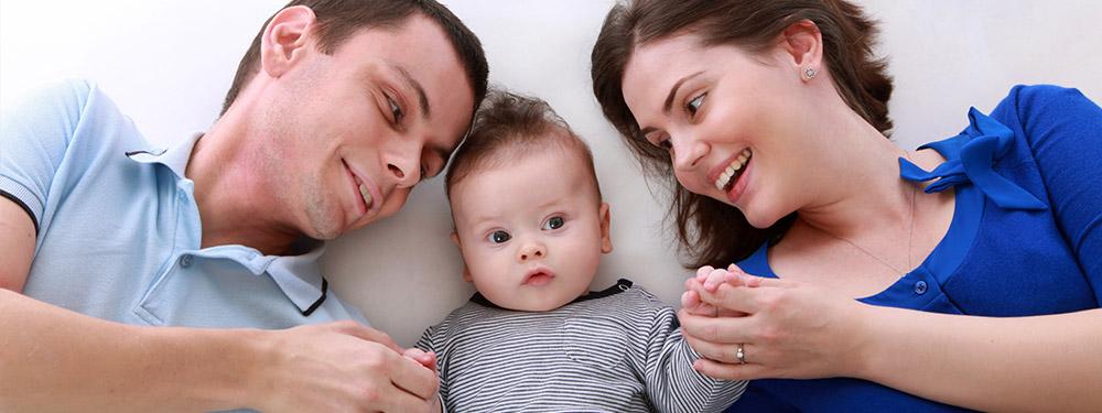 Photo de parents allongés sur un lit tenant la main de leur bébé allongé entre eux