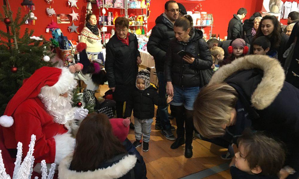 Photo du père noel en train de parler à des enfants pendant le marché de noel