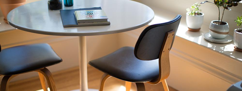 Photo d'une table ronde avec 2 chaises autour et sur cette table 3 cahiers fermés