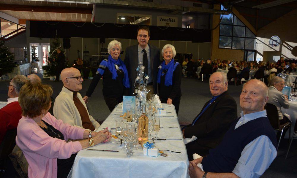 Photo du maire de Venelles posant avec les jumelles venelloises vétues de la même façon devant une table d'anciens