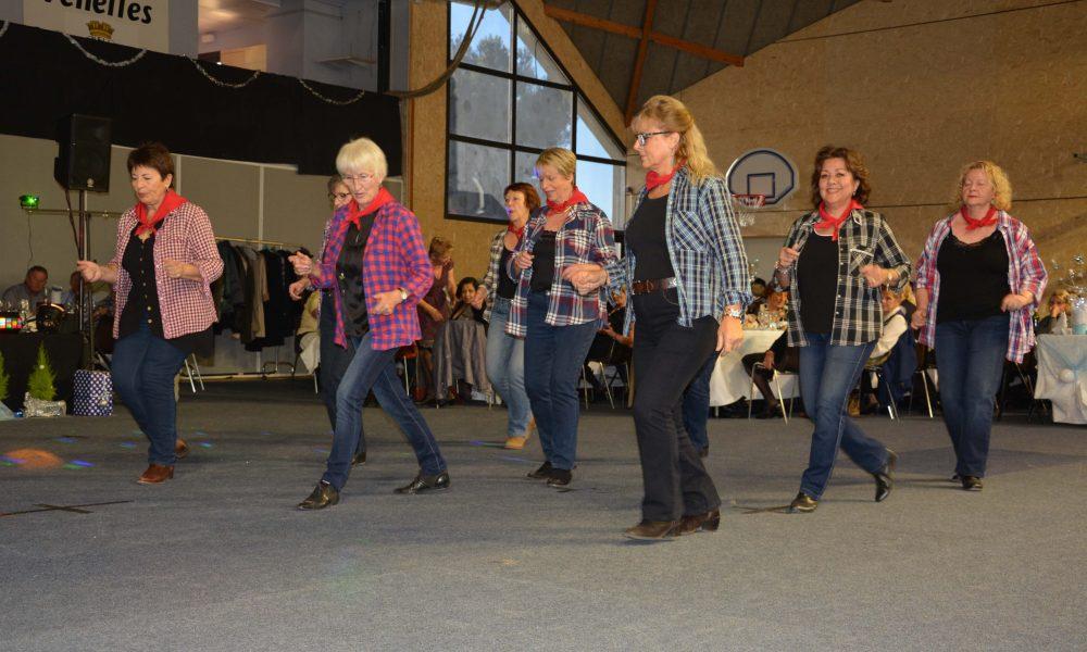Photo du spectacle de Noel avec des femmes portant chemises à carreaux, bandana autour du cou, santiags, en train de danser de la country
