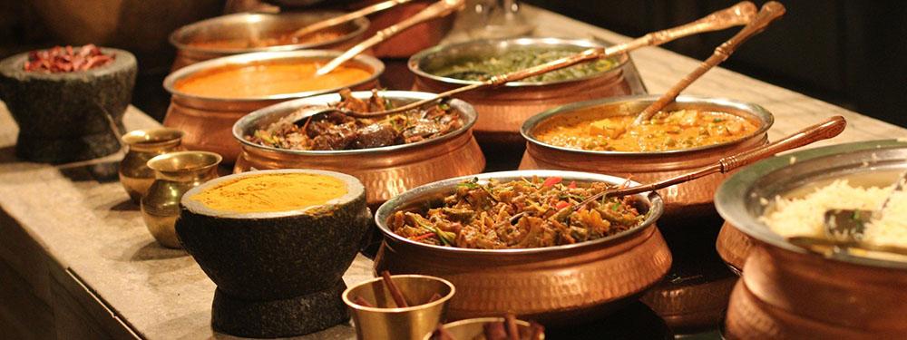 Photos représentant un buffet de plats indiens en cuivre avec des mets en sauce et des épices