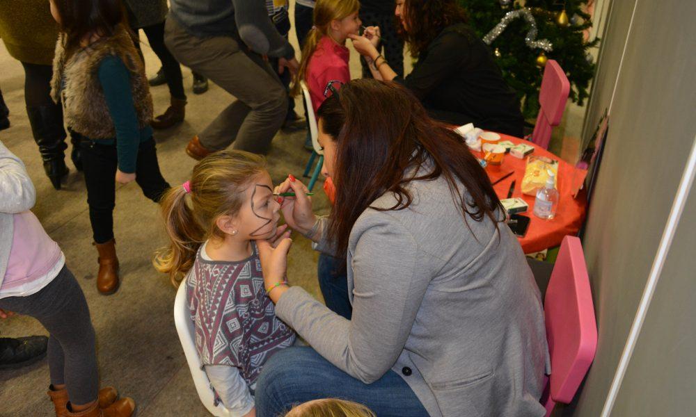 Photo d'une femme en train de dessiner un papillon sur le visage d'une petite fille lors d'un atelier maquillage