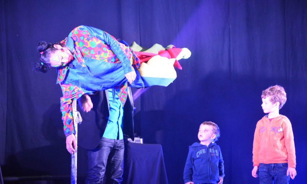 Photo d'un magicien sur scène sous les yeux ébahis de 2 enfants