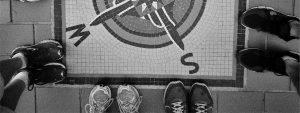 Photo d'une boussole en mozaïques au sol avec des pieds de coureurs tout autour