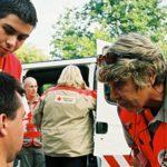 Photo d'une équipe de la Croix-Rouge Française en train de parler à un homme assis sur un banc