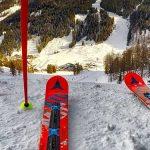 Photo zoomée sur des skis et des batons en phase de s'élancer sur la piste enneigée