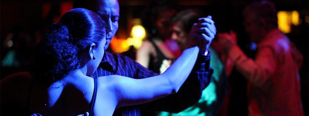 Photo d'un couple en train de danser le tango avec en fond un peu feutré d'autres couples en train de danser