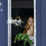Femme fumant la pipe, debout à sa fenêtre aux volets bleus
