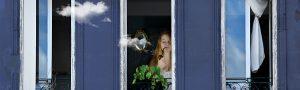 Photo d'une femme fumant la pipe, debout à sa fenêtre aux volets bleus