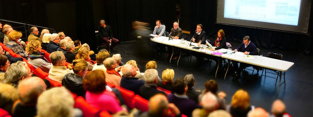 Photo d'une réunion sur le PLU avec Arnaud Mercier, les élus assis à une table face aux nombreux venellois venus prendre connaissance de cette réunion publique spéciale PLU