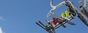 Photo vue du dessous de 4 personnes en ski assises sur un télésiège